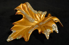 Christmas ornament - Golden leaf abstract. Golden leaf Christmas tree decoration in full on a black background Stock Image