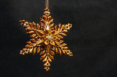 Christmas ornament - Golden Star. Ornamented golden star Christmas tree ornament on a black velvet background Stock Photography