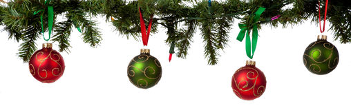 Christmas ornament hanging from garland. A christmas ornament border with red and green glittered baubles hanging from garland with red and green ribbon stock images