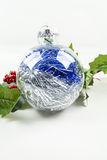 Christmas ornament and holly. A clear Christmas ornament surrounded by holly Stock Image