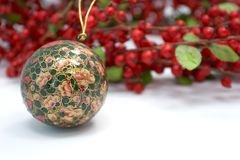 Christmas ornament and holly wreath. Christmas ornament laying beside a red holly wreath Stock Photos