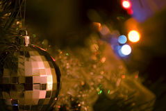 Christmas Ornament and Lights. Shiny ornament hanging on the Christmas tree reflects the colorful decoration lights. Sharp subject, blurred background stock image