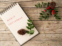 Christmas ornament and notebook on wooden background Royalty Free Stock Images