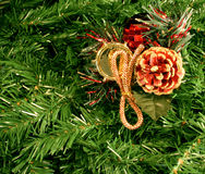 Christmas ornament on pine. Closeup of a Christmas decoration or ornament hanging from artificial pine boughs or branches Stock Images