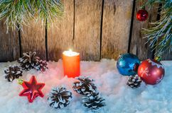 Christmas ornament, red candle and toys in the snow on a wooden background and tree branches Stock Photo