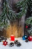 Christmas ornament, red candle and toys in the snow on a wooden background and tree branches Royalty Free Stock Image