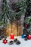 Christmas ornament, red candle and toys in the snow on a wooden background and tree branches Stock Image