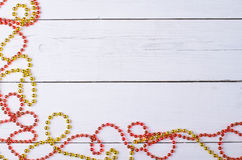 Christmas ornament, red and gold beads on a white wooden table. Stock Photography