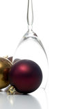 Christmas ornament series. Single upside down champagne glass surrounded by christmas ornaments, isolated on white Royalty Free Stock Photography