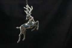 Christmas ornament - Silver Reindeer. Closeup of a silver reindeer Chrsitmas tree decoration on a black velvet background Stock Photo