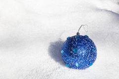 Christmas ornament on the snow. Blue Christmas ornament laying on the snow, as aconcept of Christmas Stock Image