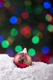 Christmas ornament on snow with colorful lights Royalty Free Stock Image