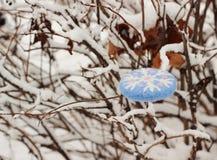 Christmas ornament snowflake. On snow branch Stock Photos