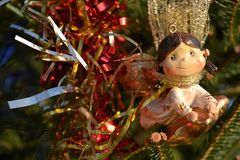 Christmas ornament toy as a girl angel flying on a star, ornating a natural fir tree in a park. Christmas ornament toy as a girl angel flying on a golden star royalty free stock images