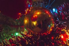 Bright Christmas tree lights and tinsel. Christmas ornament on a tree, surrounded by tinsel and Christmas lights Royalty Free Stock Photography