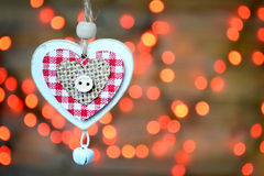 Christmas ornament: Wooden heart with jingle bell against Christmas lights Royalty Free Stock Images