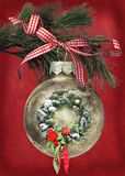 Christmas ornament with wreath. Holiday wreath in gold Christmas ornament hanging from pine bough Stock Images