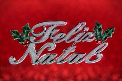Christmas ornament wrote. `Merry Christmas` greeting in portuguese isolated on red defocused background with clipping path Stock Image