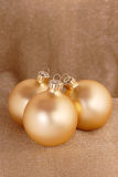 Christmas ornaments. Gold toned xmas baubles on a shimmering gold background stock photos