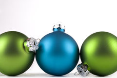 Christmas ornaments. Blue and green Christmas ornaments lined up, isolated Royalty Free Stock Image