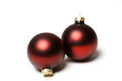 Christmas ornaments. Two red christmas tree ornaments over white Royalty Free Stock Images