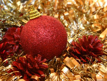 Christmas ornaments. Pine cone, christmas ball and gold ribbon Stock Photography
