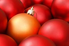 Christmas ornaments. Gold christmas bauble amongst red ornaments Stock Images
