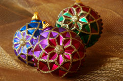 Christmas Ornaments. Colorful vintage Christmas ornaments on shiny gold netting fabric royalty free stock photo