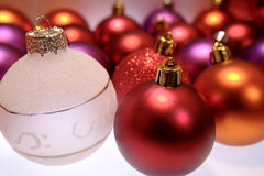 Christmas Ornaments. Array of Christmas ornaments in colors of red, purple and gold and one white frosted ornament Stock Photography