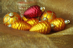 Christmas Ornaments. Red and gold vintage Christmas ornaments on gold holiday netting fabric stock images
