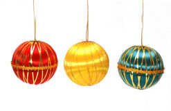 Christmas Ornaments. Three colorful Christmas ornaments hanging by strings Stock Photo