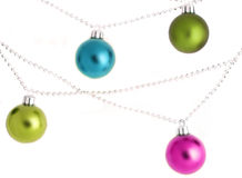 Christmas ornaments. Four colorful hanging christmas ornaments and beads Royalty Free Stock Photos