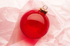 Christmas ornaments. Bright red Christmas ornament on pink tissue paper Royalty Free Stock Images