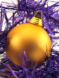 Christmas ornaments. Golden christmas ornament in violet decorative ribbon Royalty Free Stock Photo