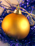 Christmas ornaments. Golden christmas ornament in violet decorative ribbon Stock Photography