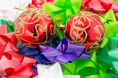 Christmas ornaments amid colorful bows Stock Photo