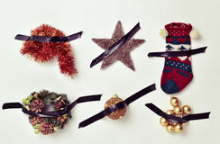Christmas ornaments attached to the wall with tape. Some different christmas ornaments, such as tinsel, a star, a stocking or baubles, attached to a white wall Stock Image