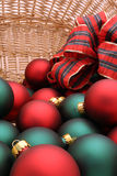Christmas Ornaments in a Basket Series - Ornaments1. Basket filled with red and green Christmas ornaments decorated with a tartan bow royalty free stock photography