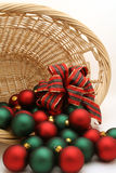 Christmas Ornaments in a Basket Series - Ornaments2. Basket filled with red and green Christmas ornaments decorated with a tartan bow royalty free stock photos