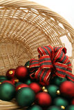 Christmas Ornaments in a Basket Series - Ornaments4. Basket filled with red and green Christmas ornaments decorated with a tartan bow stock photography