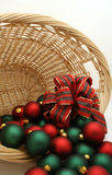 Christmas Ornaments in a Basket Series - Ornaments5. Basket filled with red and green Christmas ornaments decorated with a tartan bow royalty free stock photos