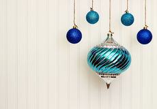 Christmas Ornaments On BeadBoard. Blue Christmas ornaments strung with jute string and hanging in front of a white bead board background for copyspace.  Large Royalty Free Stock Photography