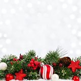 Christmas ornaments and branches in snow with twinkling background Royalty Free Stock Photography