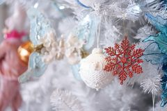 Christmas ornaments. A closed up details of Christmas decorations on a white Christmas tree with soft focus on the glitter royalty free stock image