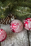 Christmas ornaments covered with snow on rustic table Stock Photo