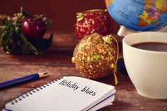 Christmas ornaments, cup of coffee, globe and text holidays blue royalty free stock images