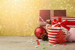 Christmas ornaments and cup with gift boxes over gold bokeh background Stock Photos