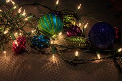 String of lights and some christmas ornaments on a garage floor. Christmas ornaments on a dark textured rubber background royalty free stock photos