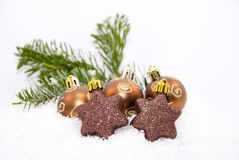 Christmas ornaments on fake snow. Some brown Christmas ornaments on fake snow Royalty Free Stock Photo