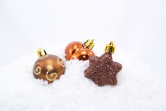 Christmas ornaments on fake snow. Some brown Christmas ornaments on fake snow stock photography
